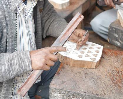 下書きに合わせ、寸分の狂いのないよう木版を彫る職人。